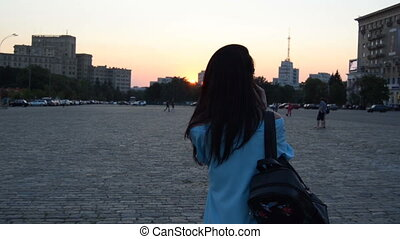 young girl with dark hair in a dress and with a backpack walks on the square of the city in the evening
