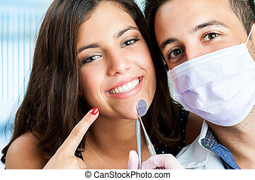 Young girl with dentist pointing at mouth