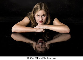 Young girl with different reflection in the mirror to symbolize a split personality