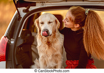 Young girl with dog in car trunk