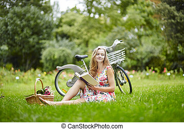 Young girl with eading a book outdoors