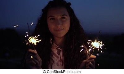 Young girl with fireworks in hands on a background of a night city. slow motion.
