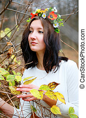 Young girl with flower wreath among branches of autumn in the park