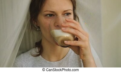 young girl with freckles drinking cappuccino and eating a...