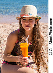 Young girl with glass of juice sitting on beach