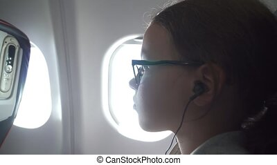 Young girl with glasses and headphones watches video on the...