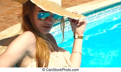 young girl with glasses stands in the pool looks into the camera and corrects Hat