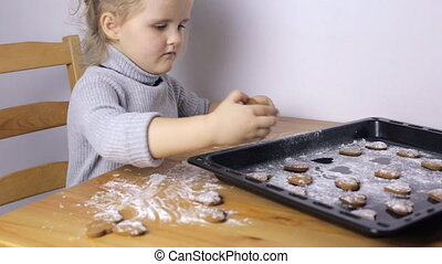 Young girl with handmade heart shaped cookies in kitchen