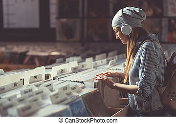 Young girl with headphones browsing records