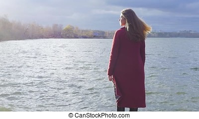 Young girl with her hair stands near the water in the cold season. Back view. Young woman standing near a lake