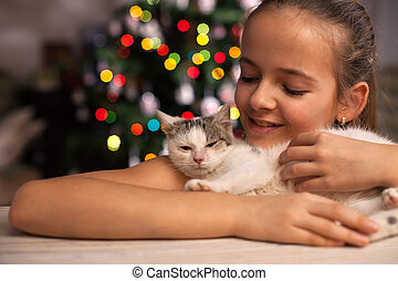 Young girl with her rescued kitten in front of the xmas tree at christmas time