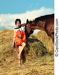 young girl with horse near hay