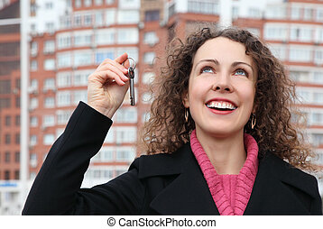 young girl with key in hand looks upwards against many-storeyed house