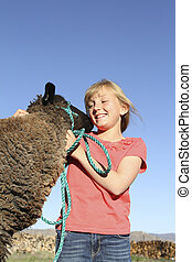 Young Girl with Lamb - a young girl playing with her pet...