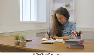 Young girl with laptop computer is doing homework. College education. Female student is studying at home.