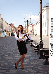 Young girl with laptop walk in old town