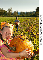 young girl with large pumpkin, in field