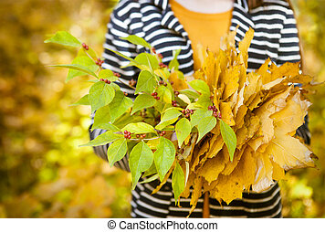 Young girl with leaves in her hands