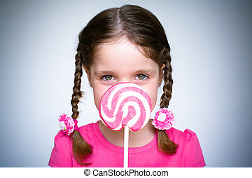 Young Girl With Lollypop - A young girl holds a large spiral...