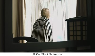 Young girl with long hair in a striped suit and black bra departs from the panoramic windows