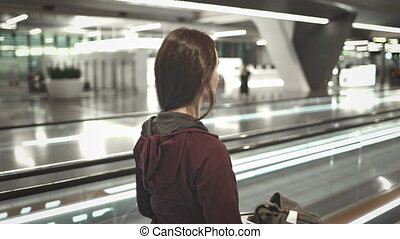 young girl with luggage walk on airport speedwalk - Young ...
