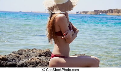 young girl with nice body in a bathing suit and hat keeps your hands on the chest sits on a rock in the sea and turns her head