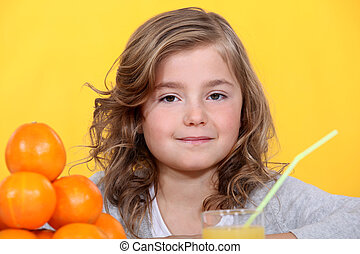 Young girl with oranges and a glass of juice