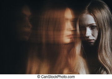 Young girl with psychiatric problem. Blurred person in the...