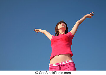 young girl with raised hands on blue sky background