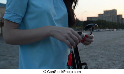 young girl with red fingernails stands on the street and...