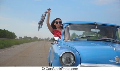 Young girl with scarf in hand leaning out of vintage car window and enjoying trip. Woman looks out of moving retro car with beautiful landscape at background. Travel concept. Slow motion Close up