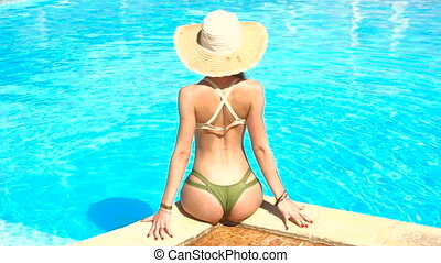 young girl with sexy buttocks in bikini sits poolside