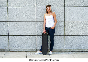 Young girl with skateboard in the city by the wall smiling.