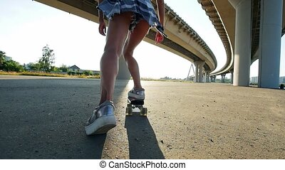 Young girl with slender legs riding a skateboard under the...