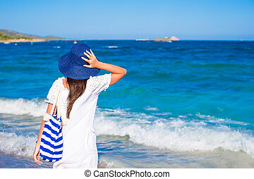 Young girl with straw hat and blue stripy bag at tropical beach