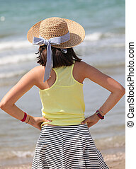 young girl with straw hat by the sea