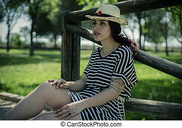 Young girl with straw hat sitting on a wooden bridge in a park in spring