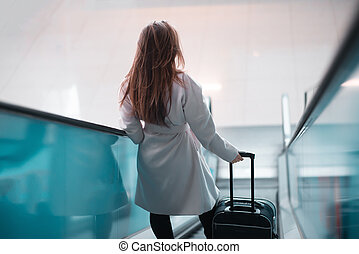 Young girl with suitcase down the escalator.