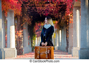 Young girl with suitcase in red grapes alley
