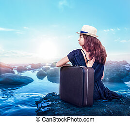 Young girl with suitcase sits on a stone.