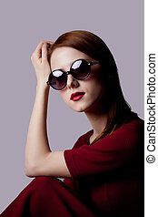 Young girl with sunglasses in red dress