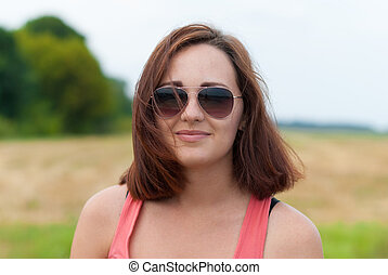 Young girl with sunglasses outdoors.