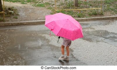 Young girl with umbrella playing in rain,