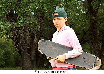 Cute young girl with well used skateboard