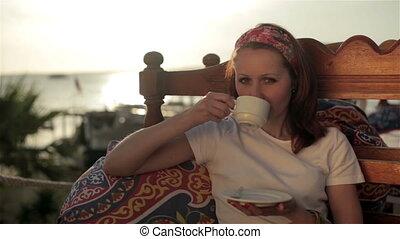 Young girl woman relaxing in cafe street veranda, drinking coffee enjoying life