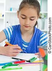 young girl working on her school project at home.