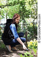 Young girl works in a spring garden, plants flowers and blow up the ground
