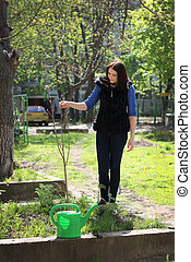 Young girl works in a spring garden, plants trees, blow the ground and watering plants