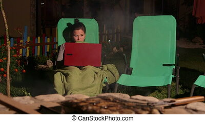 Young girl wrapped by rug sitting on lounger in backyard with laptop