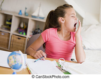 Young Girl Yawning, Doing Her Homework